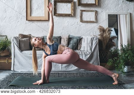 Practicing Yoga Asana At Home. Young Woman Standing In Utthita Parsvakonasana Pose Or Doing Extended