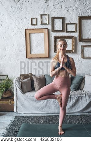 Balancing Asana. Full Length Vertical Shot Of Young Happy Woman Standing In Tree Yoga Pose In Living