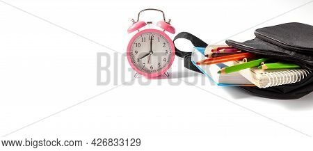 Alarm Clock 8 Am. Open School Backpack On A White Background. Books, A Notebook And Pencils Are Stic