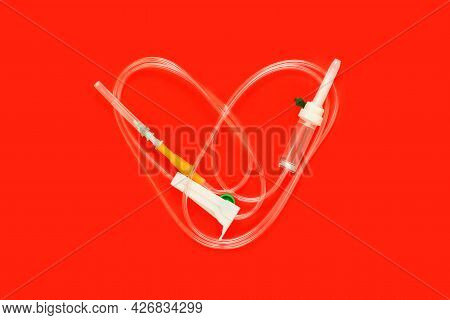 Medical Dropper In The Shape Of A Heart On A Red Background. Greeting Card For The Day Of The Medica