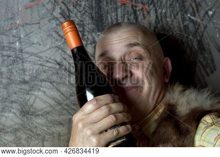 A Happy Looking Drunk Man Posing With A Bottle