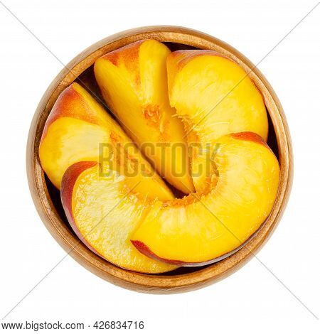 Peach Slices In A Wooden Bowl. Sliced Ripe Fruit, With A Yellow And Juicy Fruit Flesh, And With Velv