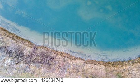 Aerial View Of A Picturesque Place Where Transparent Turquoise Water Of A Forest Lake Meets A Stony
