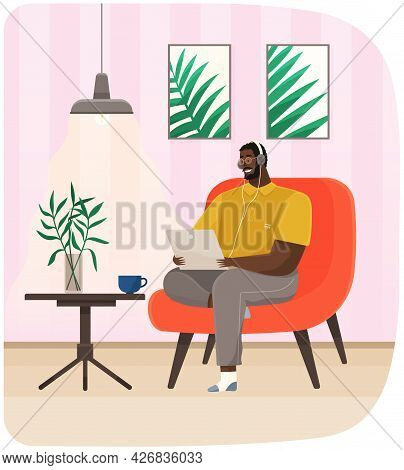 Man Sits In Chair With Laptop And Headphones. Remote Work, Freelance, Online Training Concept. Check