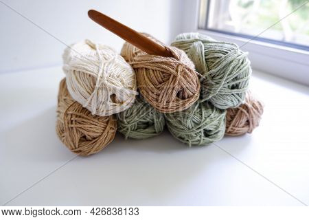 Yarn For Knitting On A White Table. Multi-colored Yarn In Soft Colors With A Crochet Hook. Needlewor
