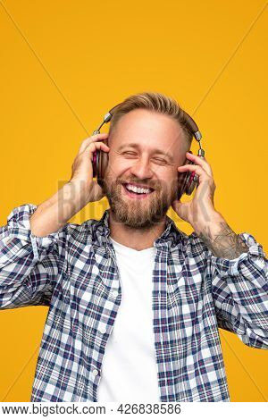 Optimistic Bearded Man In Checkered Shirt Smiling With Closed Eyes And Listening To Music In Headpho