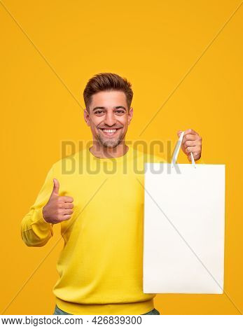 Happy Young Male Shopper Smiling For Camera And Gesturing Thumb Up While Showing Paper Bag With Purc