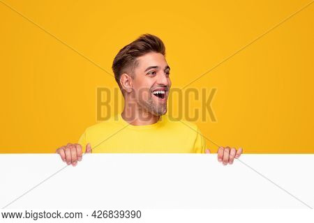 Funny Young Bearded Guy Holding Blank White Placard And Looking Away With Astonished Smile Against Y