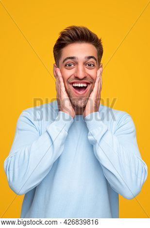 Surprised Young Guy In Blue Sweatshirt Touching Face And Looking At Camera With Opened Mouth Against