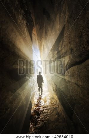 man walking out of a cave