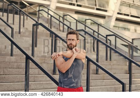Preparing His Muscles. Fitness Man Warming Up In The Gym. Having A Good Stretch. Handsome Man In Spo