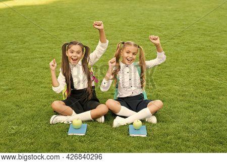 Holidays Has Begun. Happy Children Celebrate Holidays Outdoors. Little Girls Sit On Green Grass. Sch