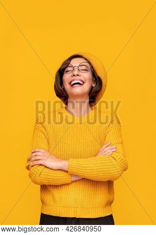 Cheerful Young Female In Vivid Knitted Sweater And Hat And Eyeglasses Laughing Brightly At Joke Agai