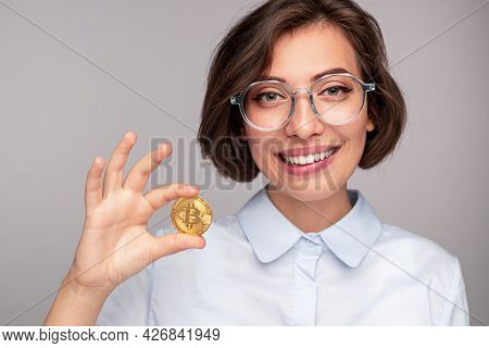 Delighted Female Investor Smiling And Looking At Camera While Demonstrating Valuable Bitcoin Against