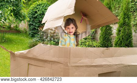 The Girl Plays In The House With A Cardboard Box. The Kid Plays In The Hostel Outdoors. The Concept