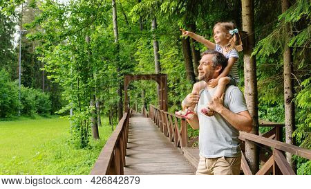 Dad Put His Daughter On His Shoulders And Tells Stories About Animals. Family Vacation In The Woods.