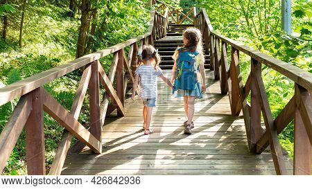 Two Cute Girlsare Heading To The Family Camp Along The Eco Trail Of The Reserve. A Beautiful Wooden