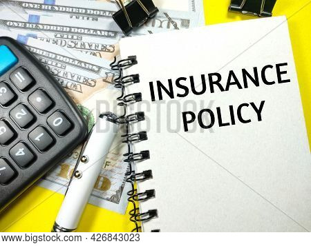 Insurance Concept.text Insurance Policy On Notebook With Pen,paper Clips,calculator And Dollar Money