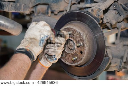 Gloved Hands Unscrew The Rear Rusted Wheel Hub With A Screwdriver. In The Garage, A Man Changes Part