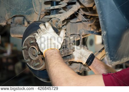 The Gloved Hands Of A Man Unscrew The Caliper On The Hub. In The Garage, A Man Changes Parts On A Ve