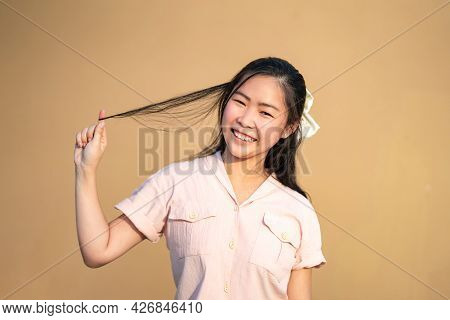 Cute Shy Asian Woman Smile And Play Her Hair In Orange Brown Background At Outdoor Field In Sunlight