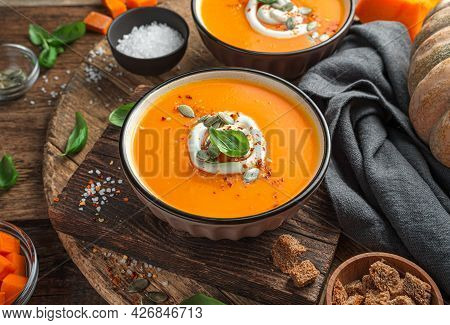 Pumpkin Cream Soup With Carrots And Cream On A Wooden Background With Ingredients. Side View, Horizo