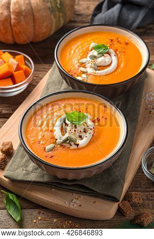 Two Bowls Of Pumpkin Soup With Basil And Cream On A Wooden Background. Vertical View, Close-up.