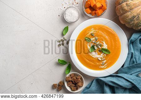Pumpkin Soup With Carrots And Cream On A Gray Background With Space For Copying. Top View. Autumn Ve