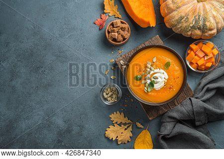 Healthy, Autumn Pumpkin Cream Soup With Cream And Basil On A Dark Blue Background With Autumn Foliag