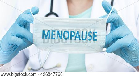 Doctor Holding A Blue Disposable Mask With Text Menopause, Medical Concept