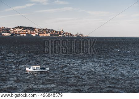 A Small Cozy Boat With Blue With Striped Curtains Inside Of Cabin Windows Sways In The Waves Of Tagu