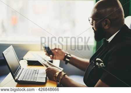 Side View Of An Elegant Black Man Entrepreneur In A Costume And Glasses, Working With Documents And