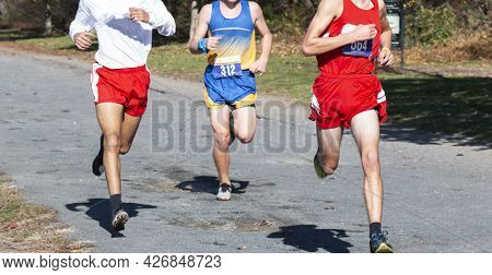 Thre High School Boys Competing In A Cross Country Running Race On A Gravel Path At Van Cortlandt Pa