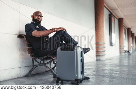 A Black Businessman On The Railroad Platform With His Bag Is Sitting On A Bench And Waiting For A Tr