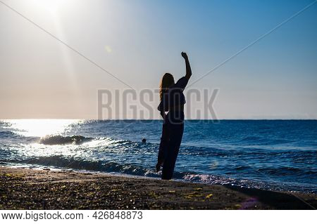 Silhouette Of Woman Stay Back On Beach