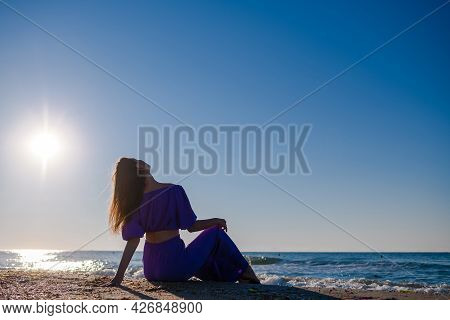 Mysterious Woman In Purple Sit On Beach