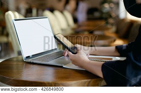 Focus On Hand Young Asian Woman Holding Smart Phone And Wearing Face Mask While She  Working At Home