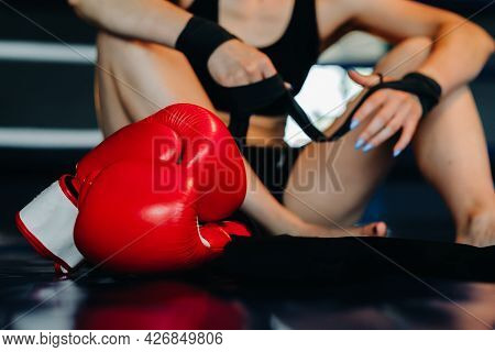 Close-up Of Red Boxing Gloves On The Floor Of A Blue Boxing Ring