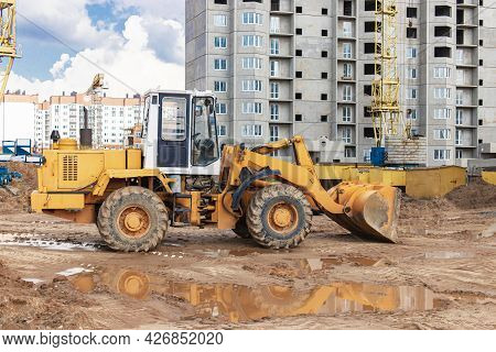 Heavy Wheel Loader With A Bucket At A Construction Site. Equipment For Earthworks, Transportation An