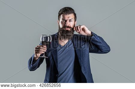 Man With A Glass Of Red Wine In His Hands. Beard Man, Bearded, Sommelier Tasting Red Wine. Sommelier