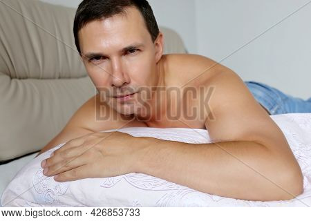 Handsome Muscular Man Lying On His Belly On A Bed And Looking Intently Into Camera