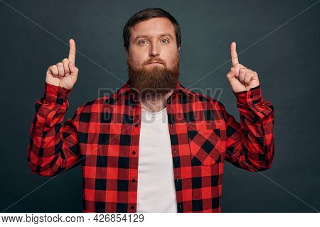 Skeptical Unsure Handsome Macho Man In Red Checkered Shirt, Pointing Up And Looking Hesitant Camera,