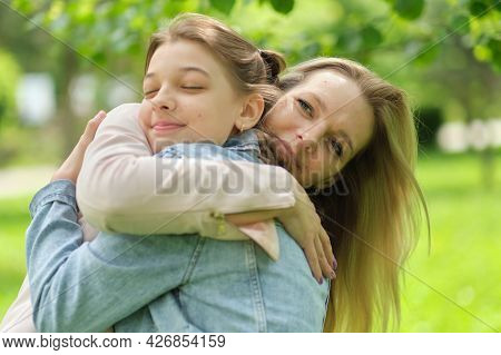 Happy Mother With Her Daughter Hugging A Teenager In The Summer. Caring Happy Mother Enjoy Day With