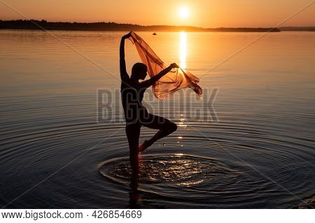 Girl Dancing In Water. Woman Practice Yoga On The Beach. Sunset Evening