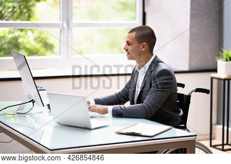 Handicapped Businessman Using Laptop Computer In Office