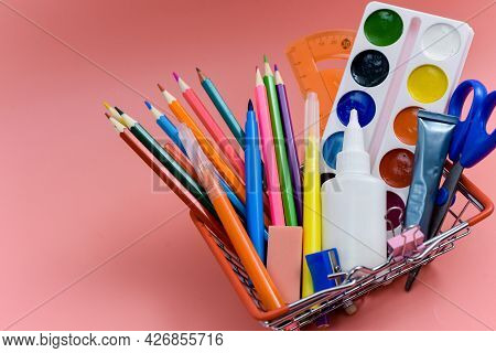 School Supplies In A Shopping Basket On A Pink Background. Preparing For School, Buying Office Suppl