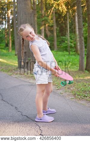 Cute Little Preteen Girl With Two Pigtails Posing With Skateboard In Beautiful Park At Sunny Day.