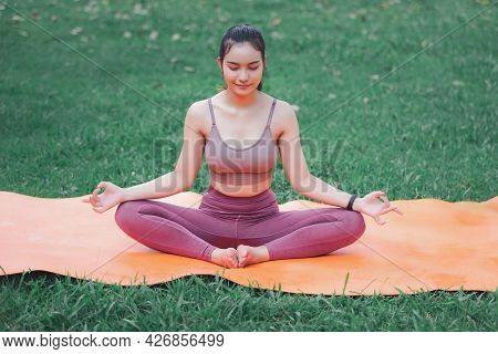 Asian Woman Practicing Yoga In Root Bond, Mula Bandha Pose On The Mat In Outdoor Park.