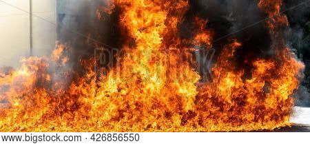 Flames Caused By The Explosion Of The Oil. Demonstration Of Water On Oil Fire. Blaze Fire Flame Text