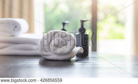 Roll Up Of White Towels With Shampoo Bottles And Liquid Soap Bottles On Table With Copy Space On Blu